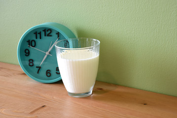 Fresh Milk in glass with clock on the wood table for Morning