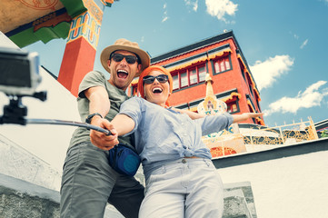Happy tourist couple take a selfie photo on asian sight backgrou