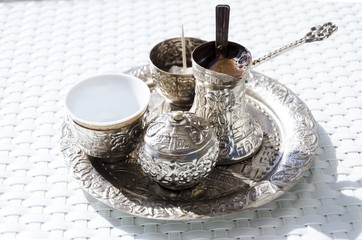 A metallic tray with copper plated cezve (dzezva) filled with traditional foam Bosnian coffee,silver pot with turkish delight,rahat lokum,clay cup and sugar cube pot served in an ornament Sarajevo set