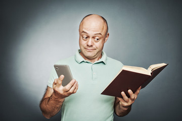 man holding a book in one hand into another smart phone