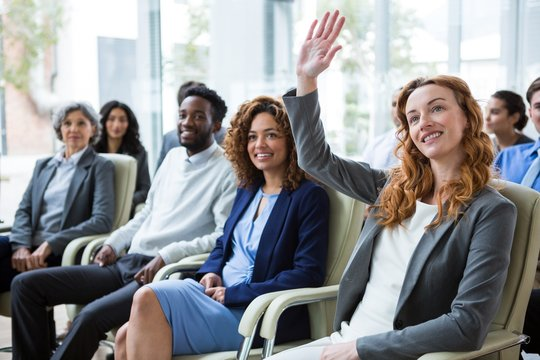 Businesswoman raising hand during meeting