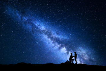 Milky Way. Night landscape with silhouettes of a man making marriage proposal to his girlfriend and starry sky. Silhouette of lovers. Couple, relationship. Blue Milky way with people. Universe