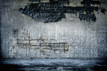 Empty room with grunge concrete wall and cement floor.