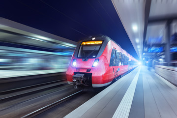 Modern high speed red passenger train moving through railway station at night. Railway station in Nuremberg. Railroad with motion blur effect. Industrial concept . Railroad travel, railway tourism