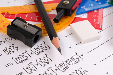 Math quadratic equation concepts. School supplies used in math. Math drawing tools with math equipment. Math exercise sheet with school supplies.