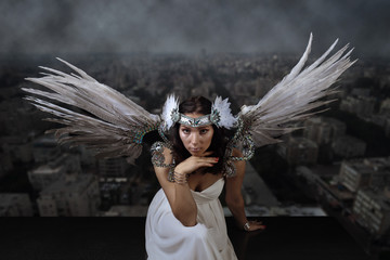 woman with angel wings on the background of the smoggy city