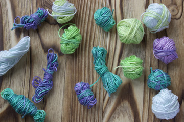 Many small multicolor melange cotton yarn balls for knitting, crochet. Wooden rustic background