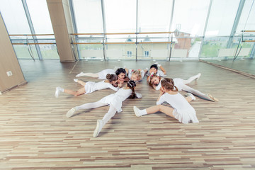 group of seven little ballerinas sitting on the floor. They are