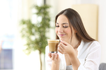Happy woman enjoying of a cup of coffee with milk