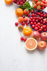 Summer fruits and berries on a white table, with space for text, selective focus