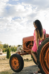 young girl in a pink dress with polka dots near the tractor, background.