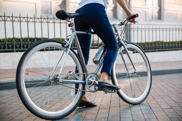 Cropped image of a female biker riding bicycle on street