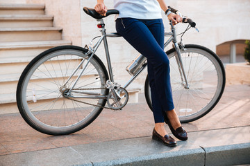 Cropped image of a female biker sitting on bicycle