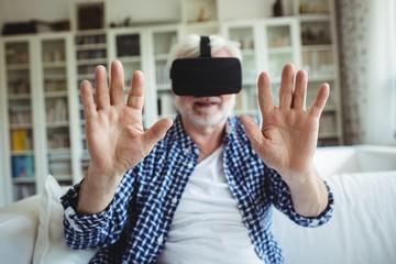 Senior man wearing virtual reality headset in living room