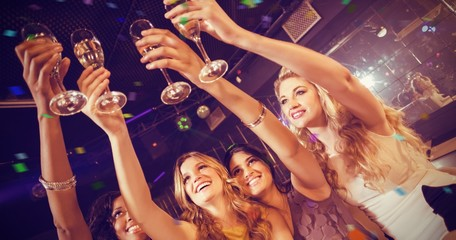 Composite image of pretty girls holding champagne glass
