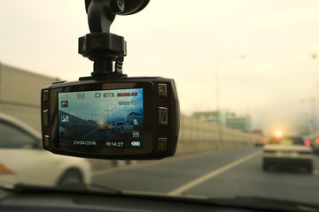 Car video recorder next to a rear view mirror in highway sunset.
