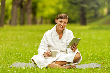 Relaxed woman using tablet, siting on the green grass in bathrob
