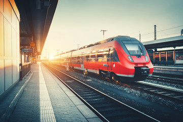 Beautiful railway station with modern high speed red commuter train at colorful sunset. Railroad with vintage toning. Train at railway platform. Industrial concept. Railway tourism