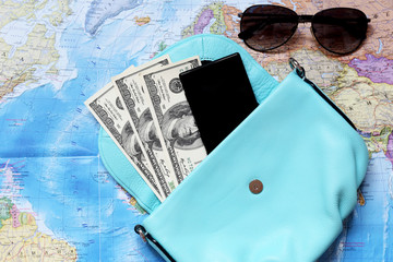 Some staff for travel. Money, glasses, bag, phone, coins are located on the intrenational map.