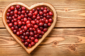 Cranberries on wooden tray on brown  wooden background.