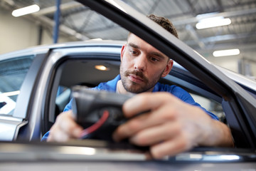 mechanic man with diagnostic scanner at car shop