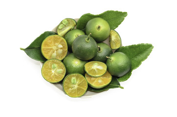 Cut limes and green leaves on white background.