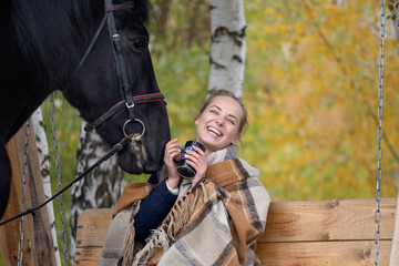 girl in a plaid with a black horse in the autumn under a birch tree on a bench