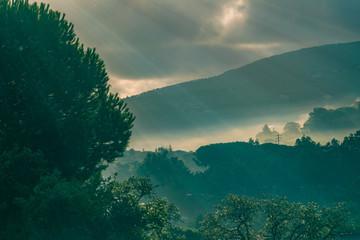 Sonnenstrahlen am Morgen scheinen druch Nebel und Wolken