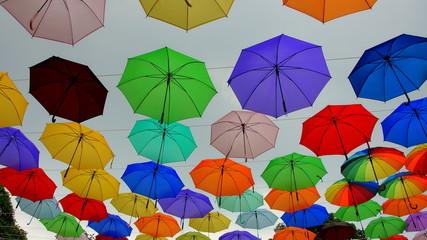 viele bunte Schirme schweben am Himmel