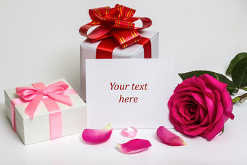 Gift box with a red ribbon and a rose.