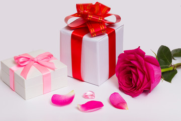 Gift boxes with bows, red ribbons, rose and petals.