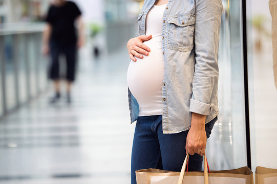 Unrecognizable pregnant woman touching her belly, holding bags,