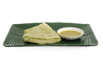 Two slices of homemade plain pancake with curry on green banana leaf plate on white background