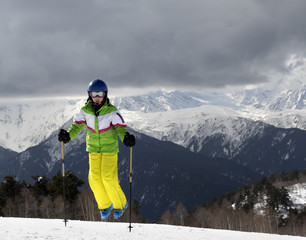 Young skier jumping with ski poles in sun mountains and cloudy g