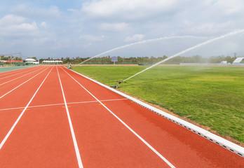 Sprinkler watering to grass field in stadium