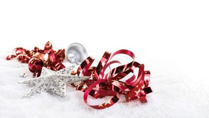 Rotes Geschenkband, Sterne und Glocke im Schnee