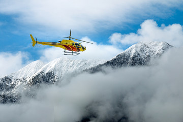 elicottero in volo tra lle montagne sopra le nuvole