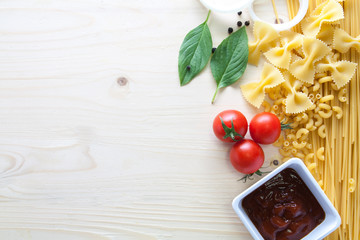 spaghetti with ingredients for cooking on wood background