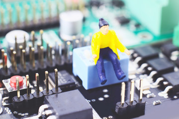 Electronic circuit with figure. Electronic background, board with miniature of man at work.