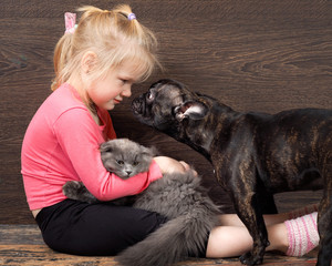 Little girl sitting on the floor with a kitten and a dog