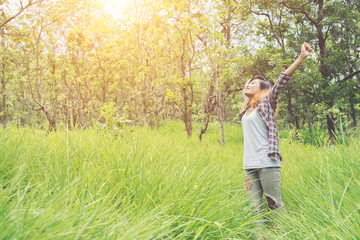 Young woman enjoying nature in the middle of a meadow,