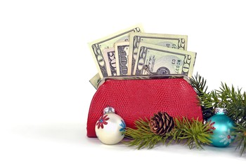 money in red purse with Christmas ornaments isolated on white