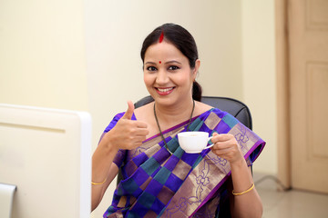 Successful traditional Indian woman making thumbs up gesture