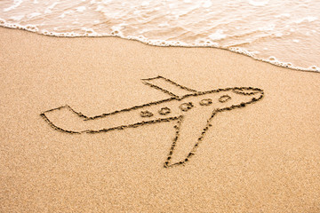 Travel to exotic country concept, the plane drawn in the sand.