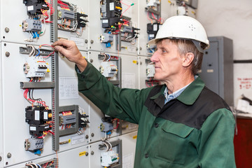 Mature electrician man working in white hard hat with cables and wires in an industrial place.