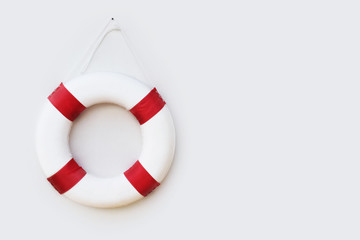 Life guards red and white rescue ring buoy hanging on white wall at the pool