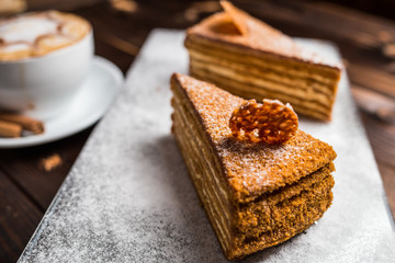 honey cake on a brown table with cup of coffe