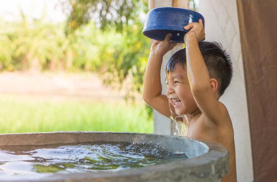 Asian village kid is taking a bath in water well.