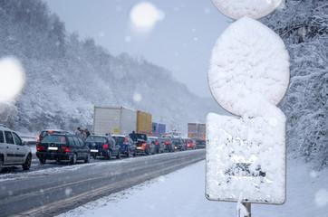 Verschneites Verkehrsschild an Autobahn – Winter Verkehrsstau Verkehrschaos