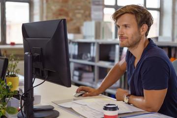 architekt sitzt am pc im büro mit bauplänen auf dem schreibtisch